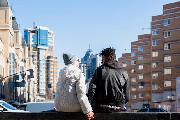Vue arrière du jeune couple interracial assis dans la rue en face des bâtiments de la ville Photo gratuit