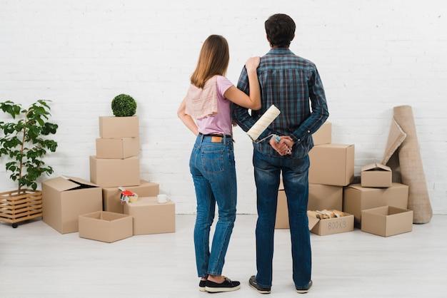 Vue arrière du jeune couple en regardant le mur peint en blanc avec des boîtes en carton Photo gratuit