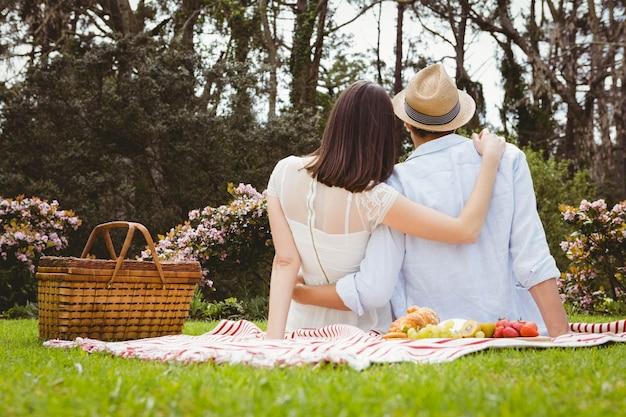 Vue arrière du jeune couple s'embrassant dans le jardin Photo Premium