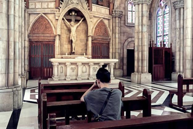 Vue arrière du jeune homme occasionnel priant dans une église. Photo Premium