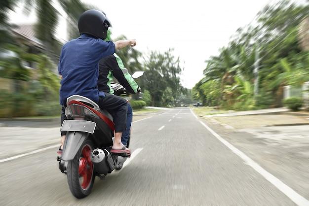 Vue arrière du passager indiquant le chemin au chauffeur de taxi moto Photo Premium