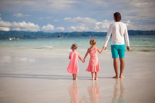 Vue arrière du père et de ses deux petites filles marchant au bord de la mer Photo Premium