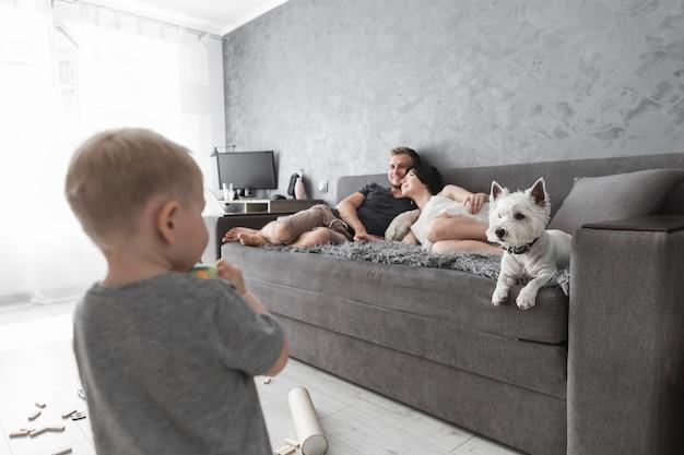 Vue arrière du petit garçon en regardant ses parents se détendre sur le canapé avec chien Photo gratuit