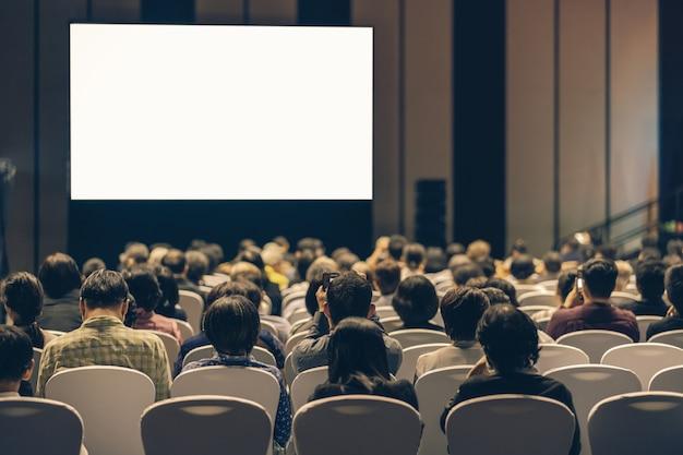 Vue arrière du public à l'écoute des intervenants sur la scène dans la salle de conférence Photo Premium