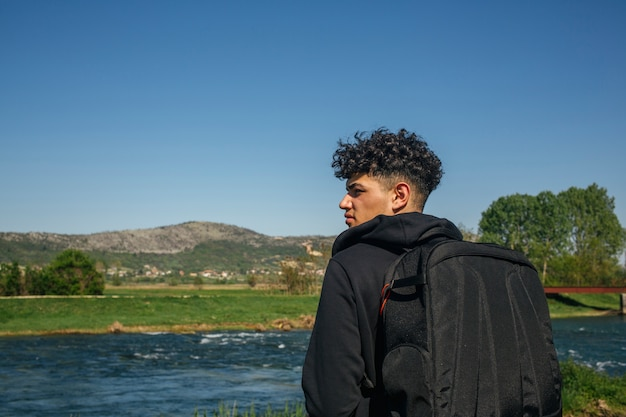 Vue arrière du touriste portant sac à dos à la recherche d'une vue panoramique Photo gratuit