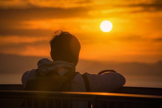 Vue arrière du voyageur homme regardant la mer au coucher du soleil à shizuoka, japon. Photo Premium
