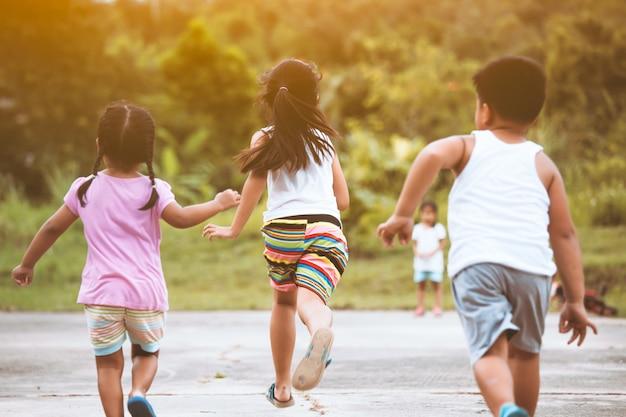 Vue arrière d'enfants asiatiques s'amusant à courir et à jouer ensemble sur le terrain Photo Premium