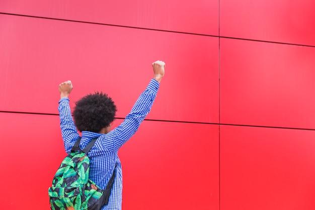 Vue Arrière, De, étudiant, Porter, Sac, à, Dos, Debout, Contre, Fond Rouge, Applaudir Photo gratuit