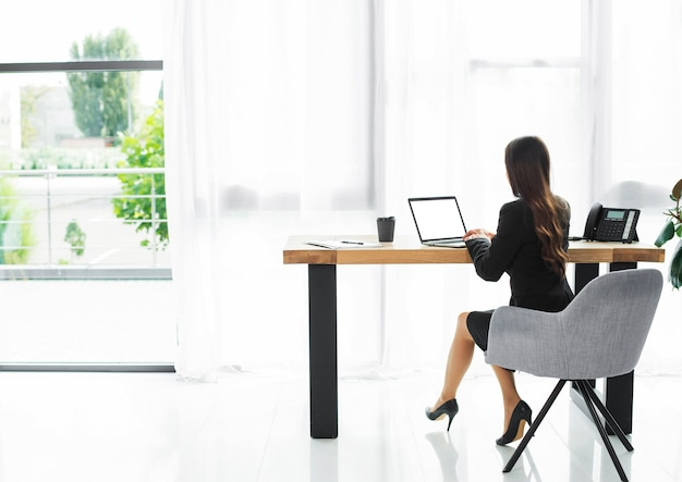 Vue arrière d'une femme d'affaires à l'aide d'un ordinateur portable à l'intérieur d'un bureau moderne Photo gratuit