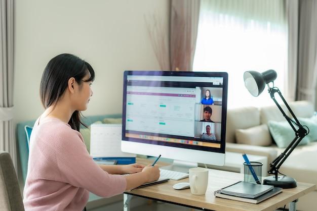 Vue Arrière De La Femme D'affaires Asiatique Parlant à Ses Collègues Du Plan En Vidéoconférence. Photo Premium