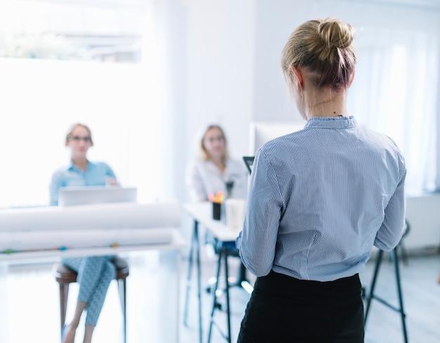 Vue arrière d'une femme d'affaires faisant une présentation lors de la réunion Photo gratuit