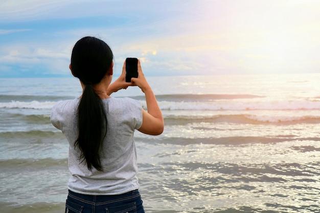 Vue arrière d'une femme asiatique aux cheveux longs, prenez une photo par téléphone portable avec la mer, la vague et le col Photo Premium