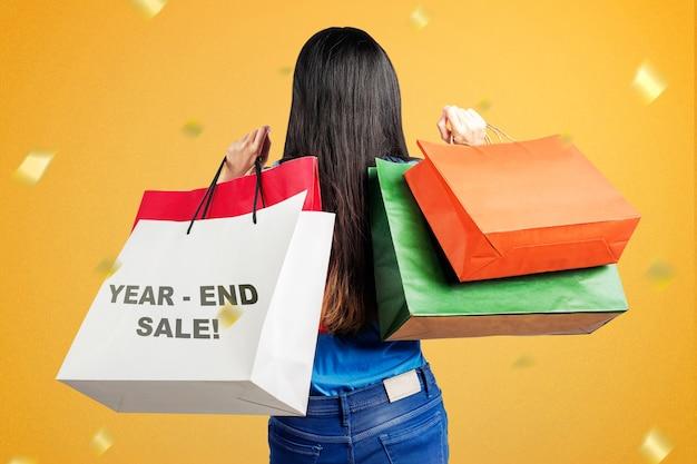 Vue Arrière De La Femme Asiatique Avec Des Sacs Après Le Shopping Sur La Vente De Fin D'année. Bonne Année 2021 Photo Premium