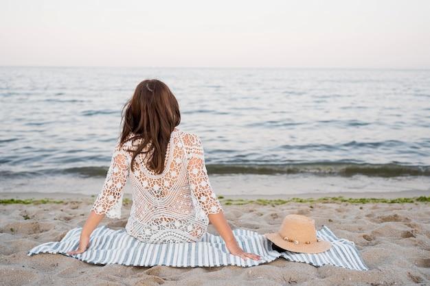 Vue Arrière Femme Assise Sur Une Couverture Photo gratuit