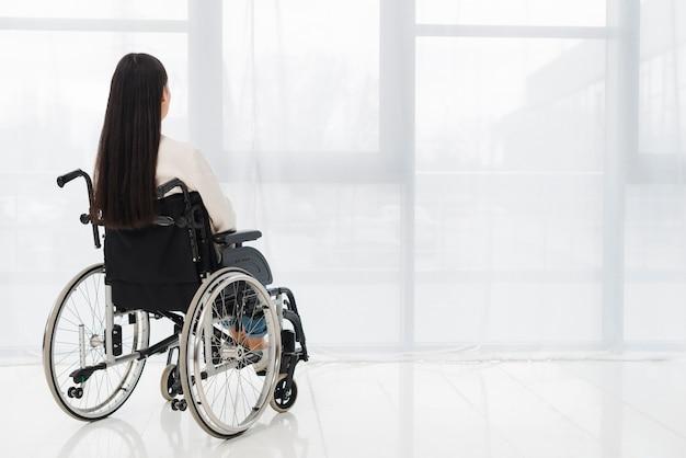 Vue Arrière D'une Femme Assise Sur Un Fauteuil Roulant, Regardant La Fenêtre Photo gratuit