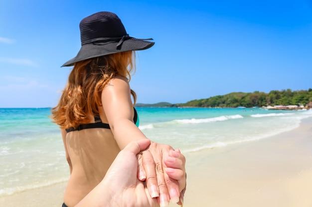 Vue Arrière D'une Femme En Bikini Avec Son Chapeau Se Promener En Tenant Son Couple Les Mains Sur La Plage Photo Premium