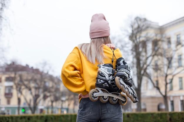 Vue Arrière De La Femme En Bonnet Portant Des Patins à Roues Alignées Photo gratuit