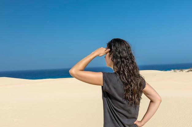 Vue arrière de la femme brune avec sa main dans son front à la recherche de la mer. Photo Premium