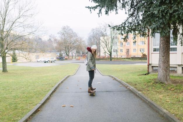 Vue arrière d'une femme à cheval sur une planche à roulettes Photo gratuit