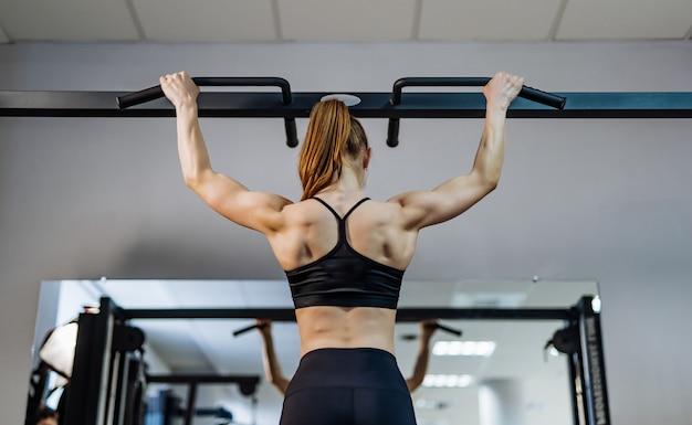 Vue arrière d'une femme avec des cheveux en queue de cheval faisant l'entraînement se resserrant sur la barre dans la salle de gym. Photo Premium