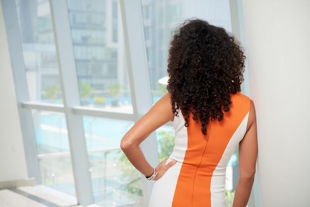 Vue arrière de la femme élégante bouclée en regardant par la fenêtre Photo gratuit