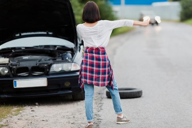 Vue arrière de la femme faisant de l'auto-stop Photo gratuit