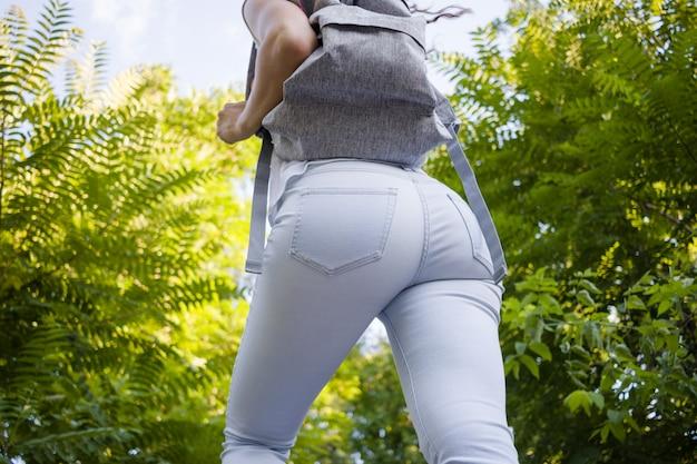 Vue arrière d'une femme mince en jeans avec un sac à dos se promène parmi les arbres verts en été Photo Premium