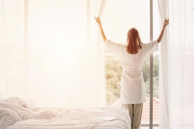 Vue arrière femme ouvrant des rideaux dans une chambre blanche Photo Premium