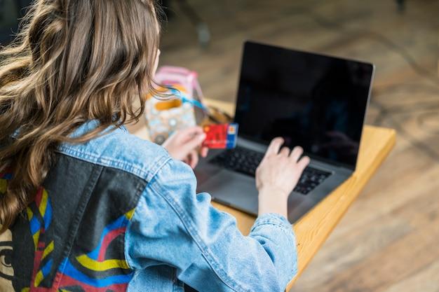 Vue arrière d'une femme tenant une carte de débit et utilisant un ordinateur portable pour faire des achats en ligne Photo gratuit