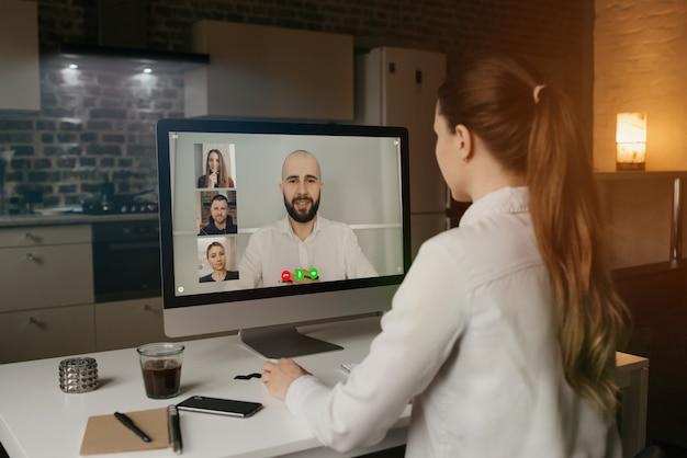 Vue Arrière D'une Femme Travaillant à Distance Pour Parler à Ses Collègues Des Affaires En Vidéoconférence Sur Un Ordinateur De Bureau à La Maison. Photo Premium