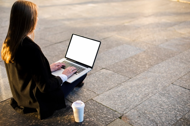 Vue arrière femme utilisant un ordinateur portable avec espace de copie Photo gratuit