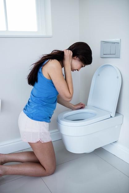 Vue arrière, de, femme, vomir, dans toilette Photo Premium