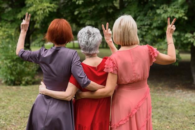 Vue arrière des femmes mûres montrant le signe de la paix Photo gratuit