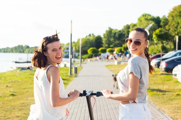 Vue arrière des femmes sur un scooter en regardant la caméra Photo gratuit