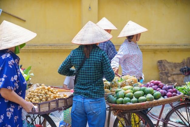 Vue arrière des femmes, vendeur de rue féminin en fruits, marché aux fleurs sur le vélo Photo Premium