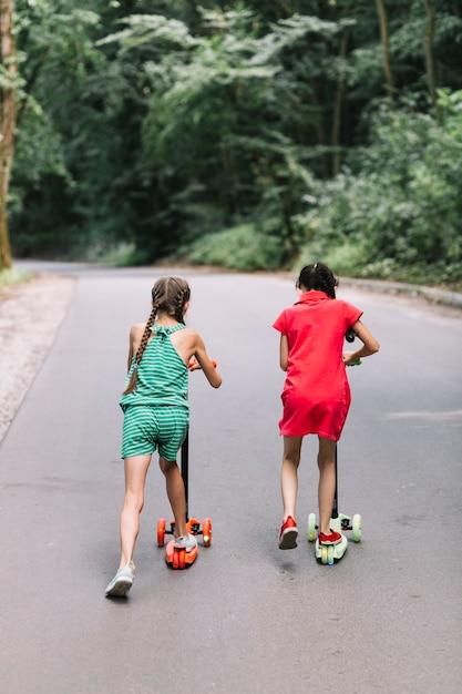 Vue arrière, de, fille, équitation, pousser, scooters, sur, route Photo gratuit