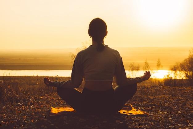 Vue arrière d'une fille méditant dans la nature au coucher du soleil. Photo Premium