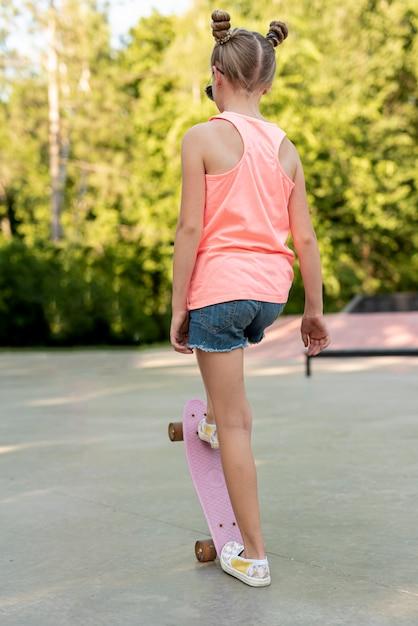 Vue arrière de la fille sur une planche à roulettes Photo gratuit