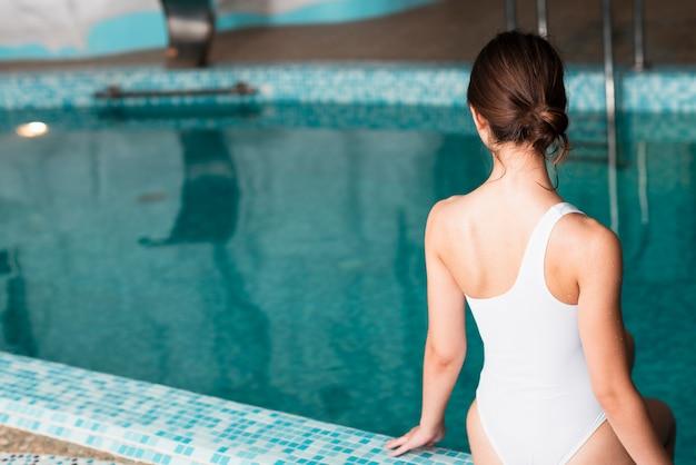 Vue arrière fille posant près de la piscine Photo gratuit