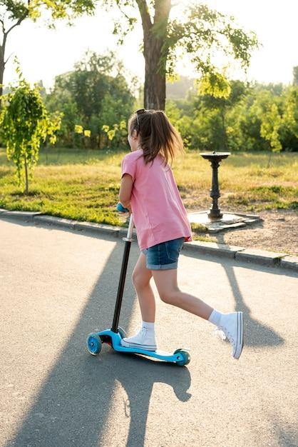Vue arrière de la fille avec un t-shirt rose sur un scooter Photo gratuit
