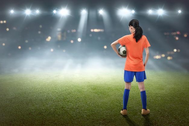 Vue arrière de la footballeuse asiatique avec le ballon Photo Premium