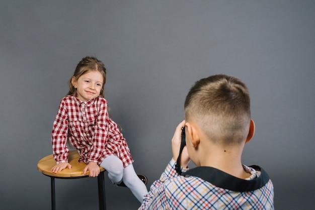 Vue arrière d'un garçon prenant la photo d'une fille souriante assise sur un tabouret de la caméra Photo gratuit