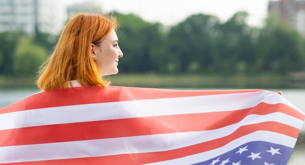 Vue Arrière De L'heureuse Jeune Femme Avec Le Drapeau National Des Usa Sur Ses épaules. Fille Positive Célébrant Le Jour De L'indépendance Des états-unis. Photo Premium