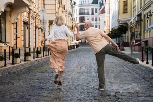 Vue Arrière De L'heureux Couple De Personnes âgées Dans La Ville Photo gratuit