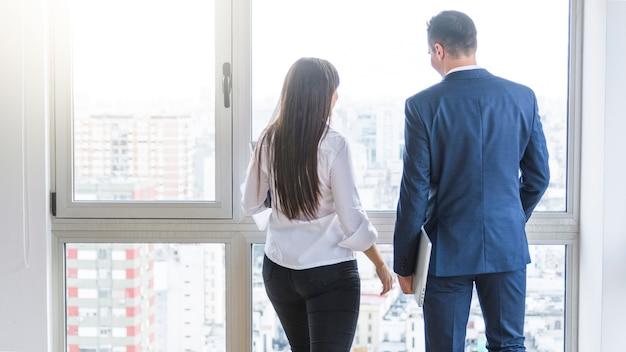 Vue arrière, de, homme affaires, et, femme affaires, regarder dehors, de, fenêtre Photo gratuit