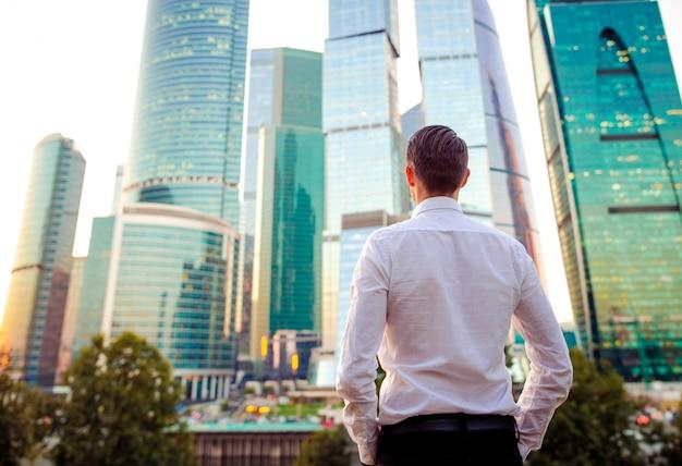 Vue Arrière De L'homme D'affaires à La Recherche Sur L'espace De La Copie En Se Tenant Debout Contre Le Gratte-ciel De Verre Photo Premium