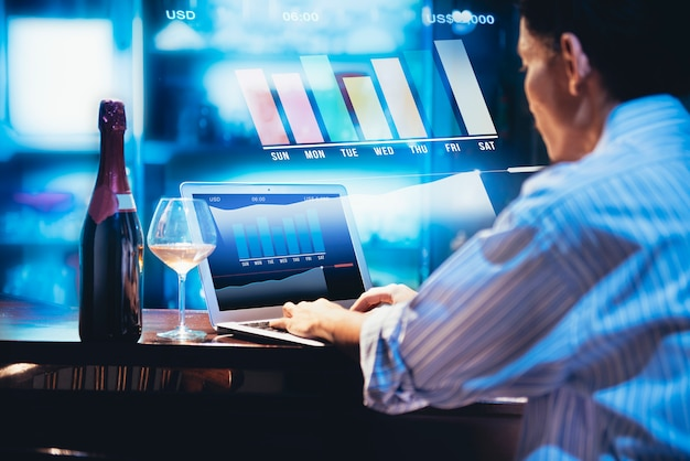 Vue arrière de l'homme d'affaires travaillant avec un ordinateur portable et une bouteille de vin Photo Premium