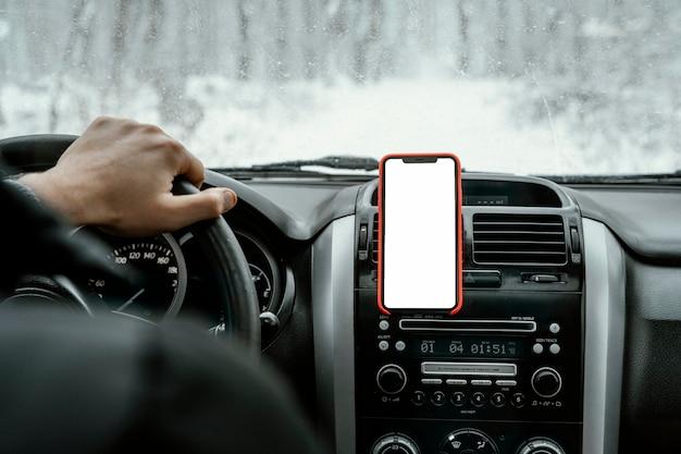 Vue Arrière De L'homme Au Volant De La Voiture Pour Un Road Trip Avec Smartphone Photo gratuit