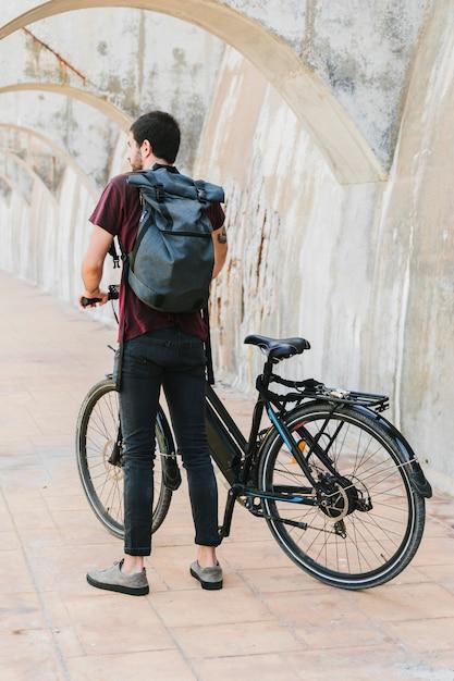 Vue arrière d'un homme debout à côté d'un vélo électrique Photo gratuit