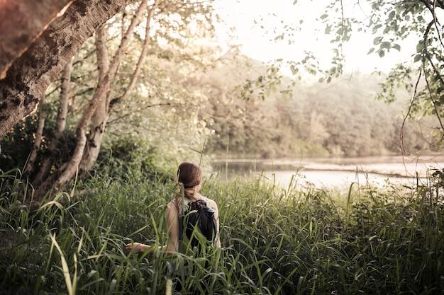 Vue arrière de l'homme debout dans l'herbe en regardant le lac Photo gratuit